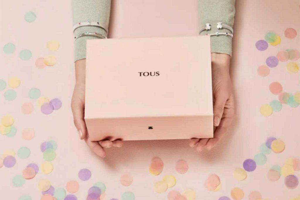 Modelo con joyas Tous en sus antebrazos sostiene una caja de Tous
