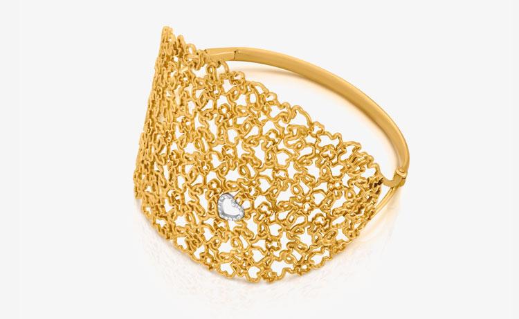 Joyas Tous - Anillo de oro hecho a base de siluetas de mini osos tous entrelazados y el detalle de un pequeño corazón.